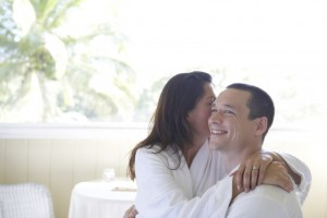 Man and young woman in bathrobes, woman sitting on man's lap