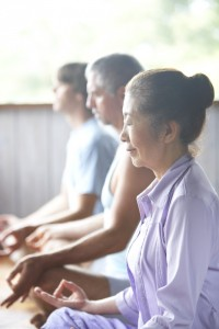 Three people meditating in yoga class, side view (focus on woman)